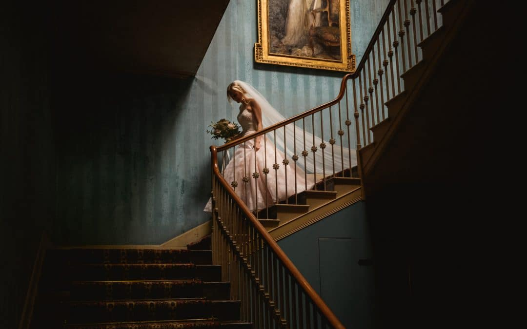 Jenni-walks-down-stairs-at-St-Giles-Hosue-captured by wedding-photographer-Robin-Goodlad